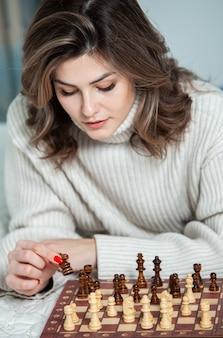 家でチェスをしている美しい少女。
