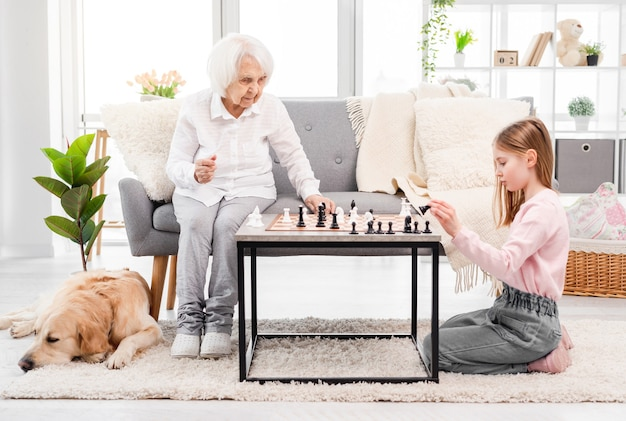 日光と床で寝ているゴールデンレトリバー犬と一緒に部屋で彼女の祖母とチェスをしている美しい少女