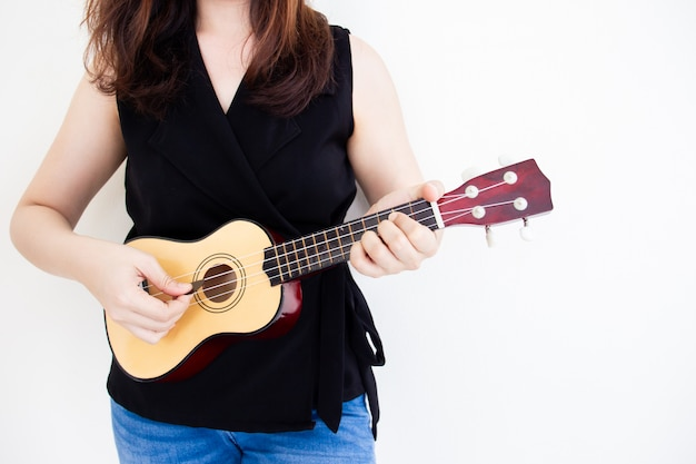 Beautiful girl playing a classic ukulele close up with copy space on right side.