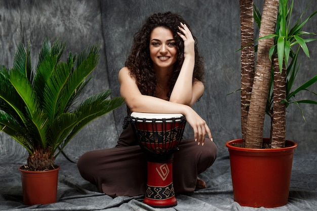 Beautiful girl playing drum in tropical plants over grey wall