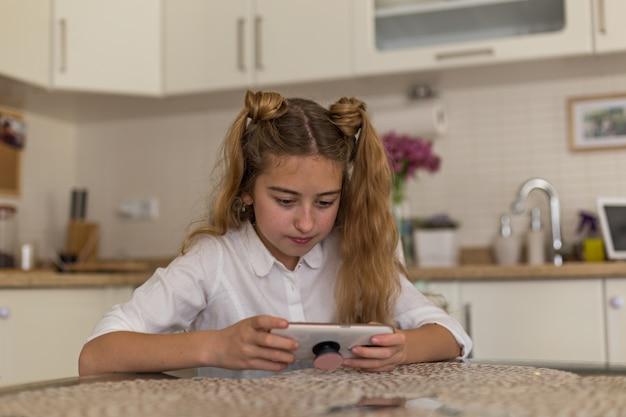 美しい少女は、キッチンの白いシャツで、スマートフォンでゲームをプレイします。