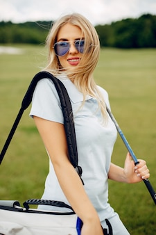 Beautiful girl playing golf on a golf course