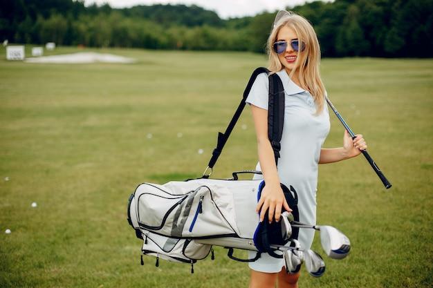 골프 코스에서 골프를 재생하는 아름 다운 여자