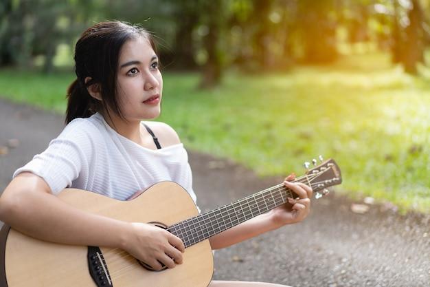 庭でギターを弾く美少女