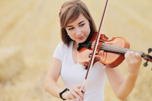 Beautiful  girl playing the violin in the field