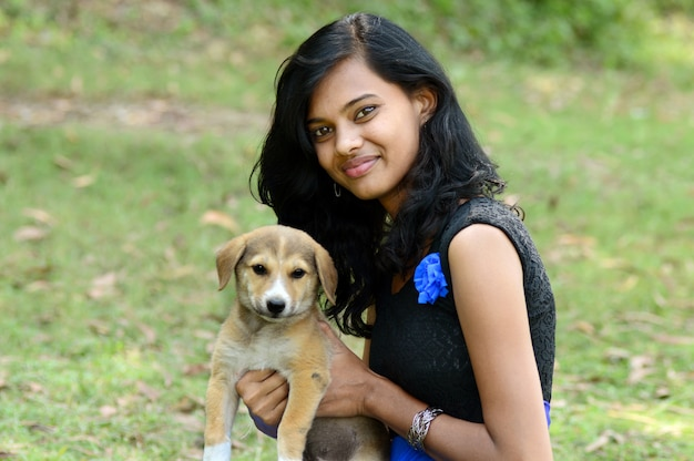 Beautiful girl playing with puppy dog in park outdoors