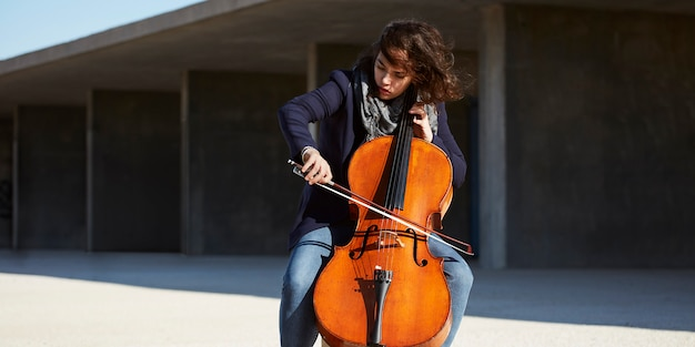 Beautiful girl plays the cello with passion in a concrete environment