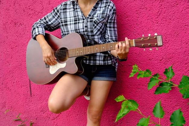 美しい少女はピンクの背景にアコースティックギターギタリストを演奏ハンサムな若いアコースティック