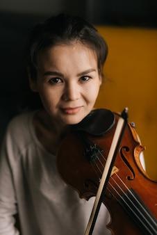 Красивая девушка играет на скрипке и смотрит в камеру. прекрасная молодая женщина играет на скрипке, сидя на мягком стуле в комнате с современным интерьером.