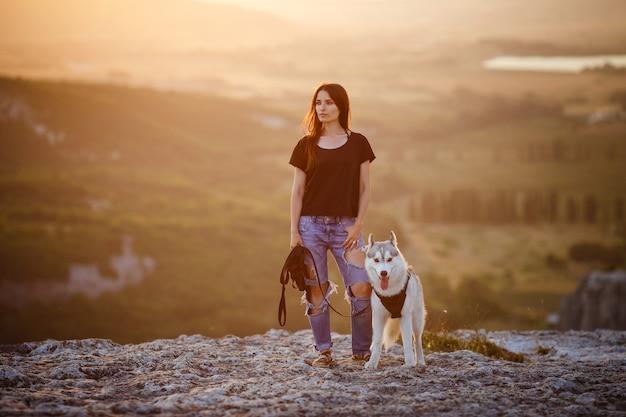 美しい少女は、日没時に山で、灰色と白のハスキー犬と遊ぶ。インドの少女と彼女のオオカミ