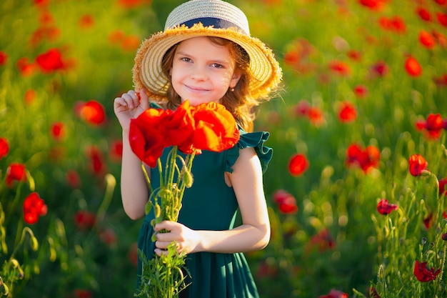 Beautiful girl in poppy field enjoys the beauty and aromas