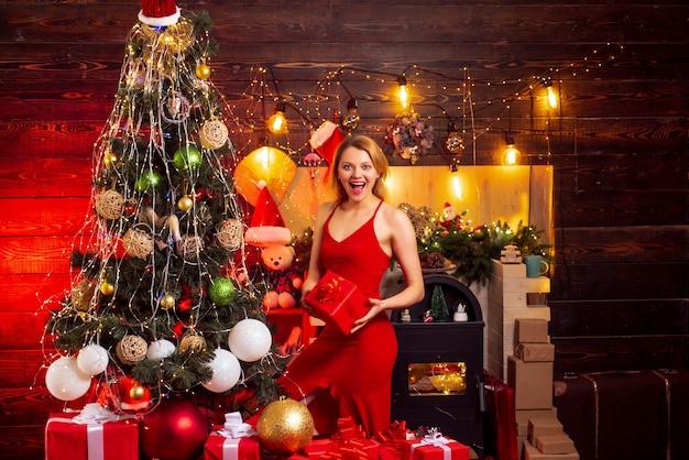 Beautiful girl portrait christmas woman dress happy woman in red dress near christmas tree new year ...