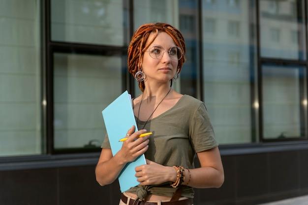 Красивая девушка позирует на фоне офисного здания. съемка для делового журнала