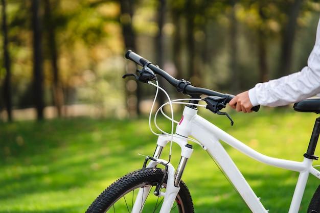Красивая девушка позирует на белом велосипеде. прогулка на природе. здоровый образ жизни.