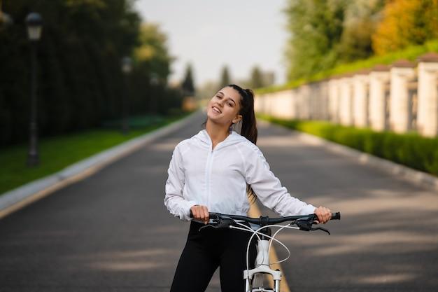 白い自転車でポーズをとる美しい少女。自然の中を歩きます。