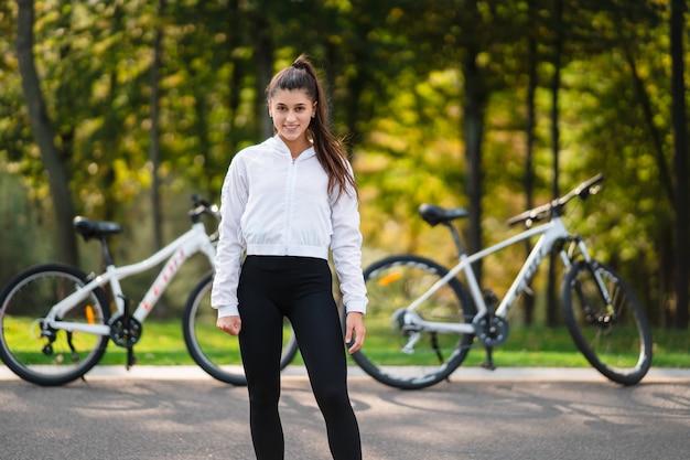 Красивая девушка позирует на белом велосипеде. прогулка на природе.