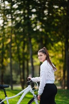 흰색 자전거에 포즈를 취하는 아름 다운 소녀. 자연 속에서 걸어보세요.