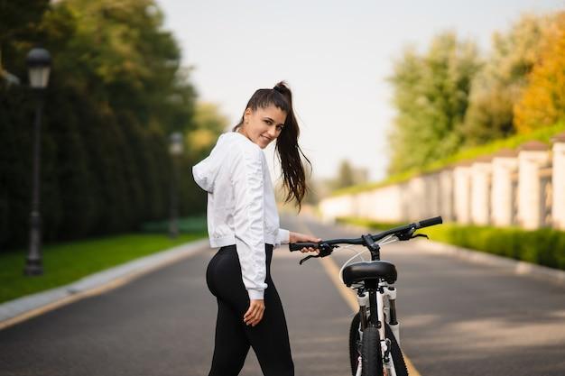 흰색 자전거에 포즈를 취하는 아름 다운 소녀