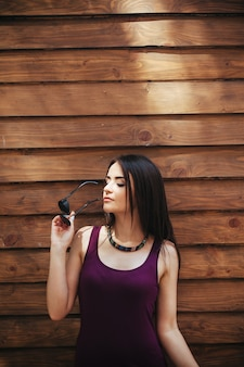 Beautiful girl posing on brown wall
