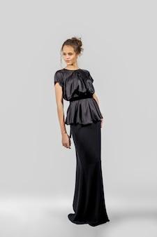 Beautiful girl posing in evening dress. full length portrait of fashion model.