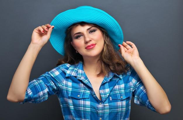 회색 배경에 파란색 모자에 포즈를 취하는 아름 다운 소녀. 스튜디오에서 찍은 사진.