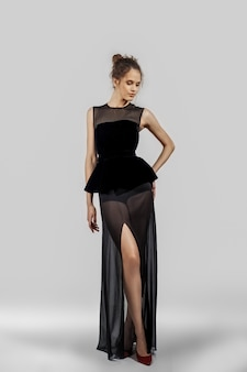 Красивая девушка позирует в вечернем платье. полная длина портрет фотомодели.