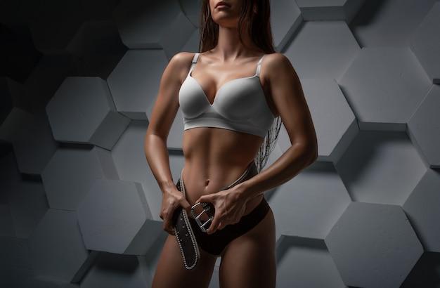 Красивая девушка позирует в тренажерном зале с поясом. концепция спорта, фитнеса и бодибилдинга. смешанная техника