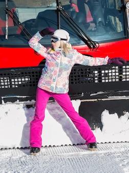 Красивая девушка позирует возле снегоочистителя в горах на снегу