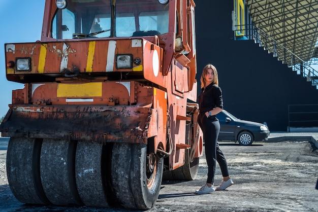 舗装機の近くでポーズをとる美しい少女。ライフスタイル
