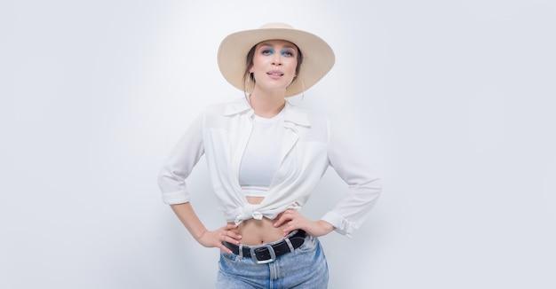 Красивая девушка позирует на белом фоне в желтой шляпе. концепция туризма. смешанная техника