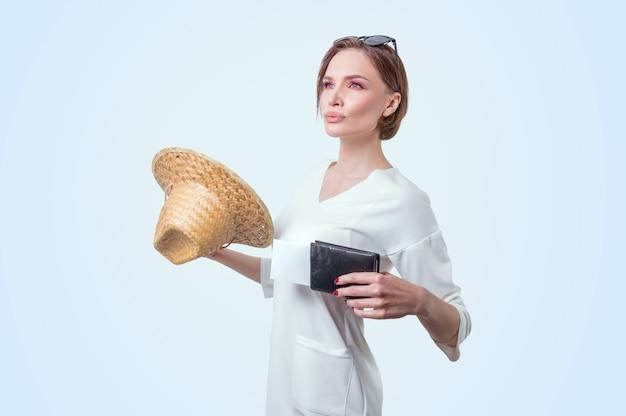 Красивая девушка позирует на белом фоне в желтой шляпе с паспортом и посадочным талоном. концепция туризма. смешанная техника