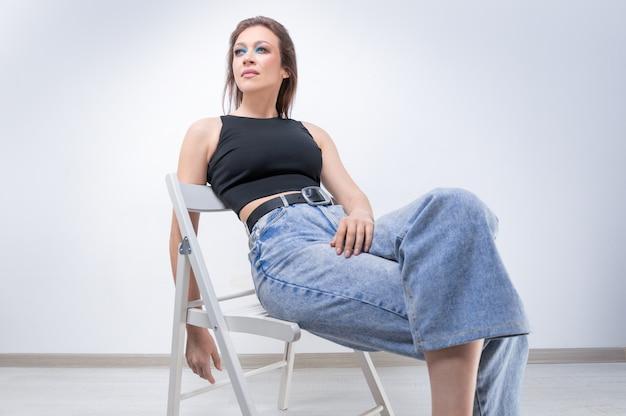 Красивая девушка позирует на белом фоне, сидя на стуле в черном боди и джинсах. рекламная концепция нижнего белья. смешанная техника
