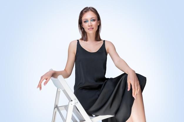 Красивая девушка позирует на белом фоне, сидя на стуле в черном пеньюаре. рекламная концепция нижнего белья. смешанная техника