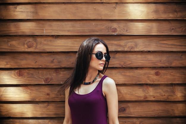 갈색 벽에 포즈를 취하는 아름다운 소녀