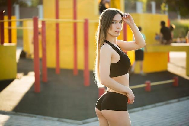 Красивая девушка позирует на спортивной площадке