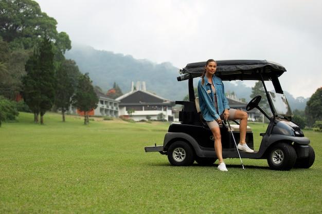 골프 코스에서 포즈를 취하는 아름다운 소녀
