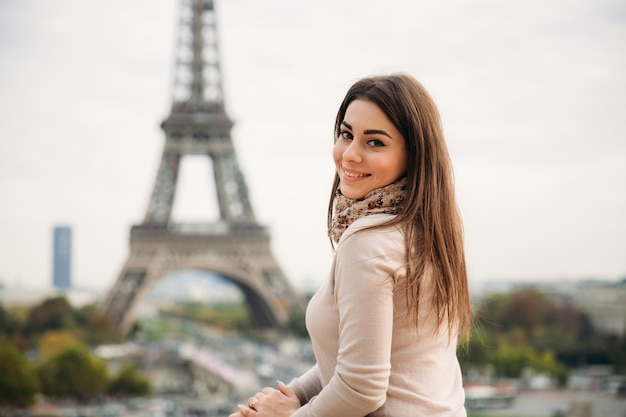 Beautiful girl posing to the photographer against the background of the eiffel tower. autumn
