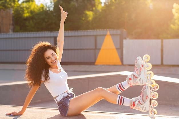 Bella ragazza in posa in rollerblades all'aperto