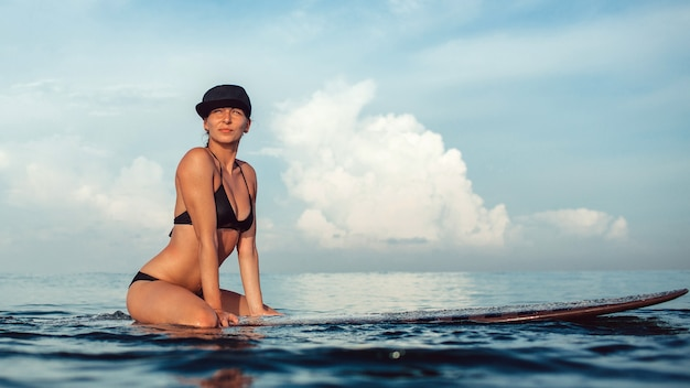 Beautiful girl posing sitting on a surfboard in the ocean