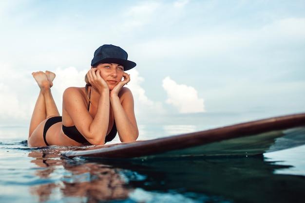 Beautiful girl posing sitting on a surfboard in the ocean