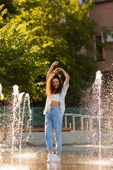 Красивая девушка позирует в окружении фонтана