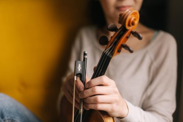 Красивая девушка позирует со скрипкой в мягком кресле. женщина-скрипач держит свой инструмент в руках. лица женщины не видно. девушка позирует с музыкальным инструментом.
