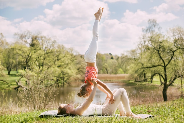 A beautiful girl practices yoga with her charming daughter.
