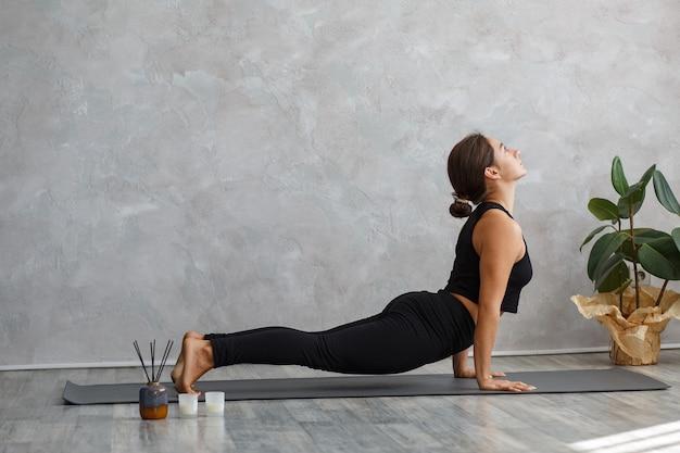 Красивая девушка практикует позу йоги кобры.