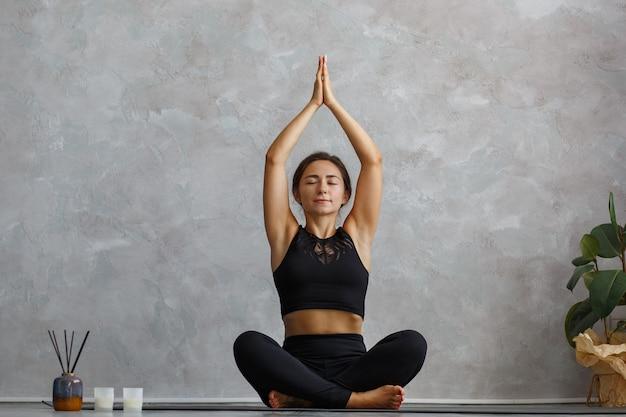 Красивая девушка практикует легкую позу йоги, сукхасану.