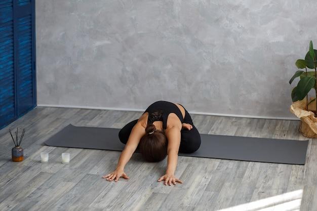 Красивая девушка практикует позу лотоса йоги, падмасана.