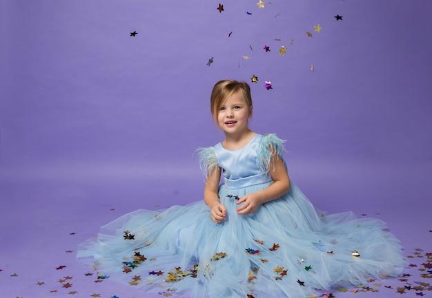 Beautiful girl in princess dress sitting with confetti on purple