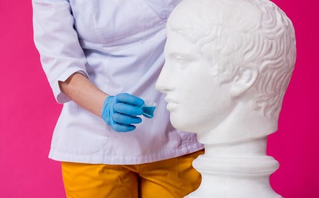 아름다운 소녀가 골동품 동상에 구강 세정제를 제안합니다.