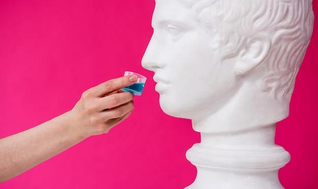 아름다운 소녀가 골동품 동상에 구강 세척제를 제안합니다.