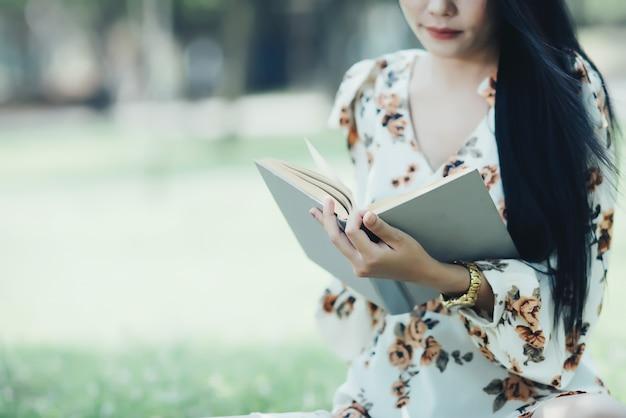 여름 태양 빛에 공원에서 아름 다운 소녀 낭독 서